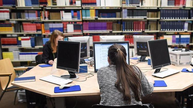 Studentinnen sitzen während einer Langen Nacht der aufgeschobenen Hausarbeiten in einer Bibliothek. Foto: Maja Hitij/Archivbild