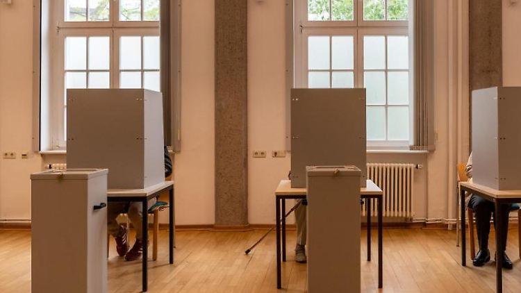 Bürger sitzen im Wahllokal in Wahlkabinen. Foto: Robert Michael/Archivbild