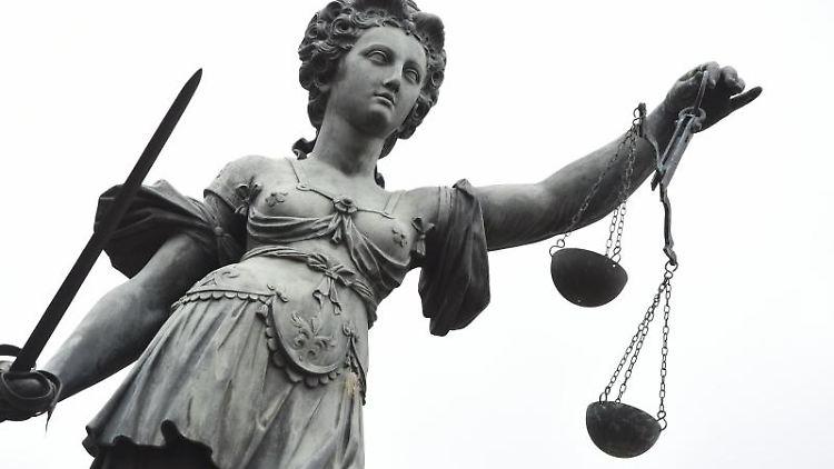 Eine Bronzestatue der Justitia steht in Frankfurt am Main. Foto: Arne Dedert/Archivbild