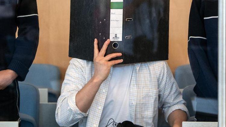 Der Angeklagte hält sich einen Aktenordner vor das Gesicht. Foto:Federico Gambarini/Archivbild