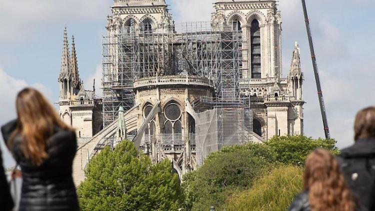 Ein Kran steht neben der Pariser Kathedrale Notre-Dame, die von Besuchern der Stadt betrachtet wird. Foto:Marcel Kusch/Archivbild