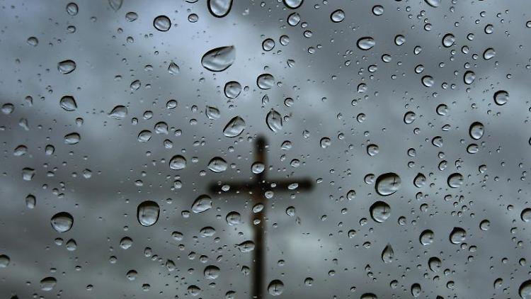 Ein Kreuz steht vor bedecktem Himmel, fotografiert durch eine regennasse Fensterscheibe. Foto: Karl-Josef Hildenbrand/Archivbild
