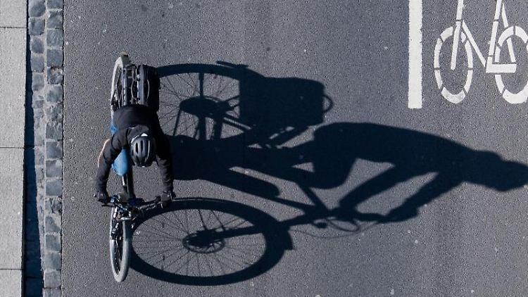 Eine Fahrradfahrerin fährt über eine Straße mit einer Markierung für Fahrräder. Foto: Julian Stratenschulte/Archivbild