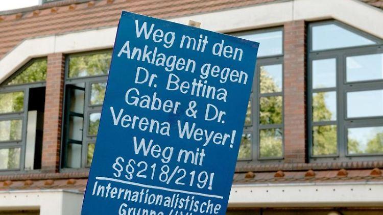 Ein Demonstrant hält ein Plakat vor dem Amtsgericht. Foto: Paul Zinken