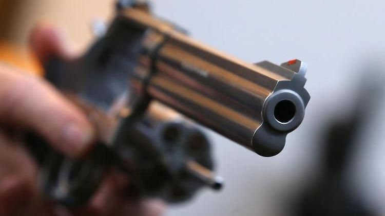 Ein Mann hält in einem Waffengeschäft einen Revolver des Herstellers Smith & Wesson. Foto: Karl-Josef Hildenbrand/Archivbild