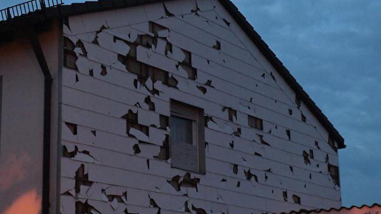 Eine durch Hagel bei einem Unwetter beschädigte Verkleidung einer Hauswand ist in der Abenddämmerung zu sehen. Foto: Felix Hörhager