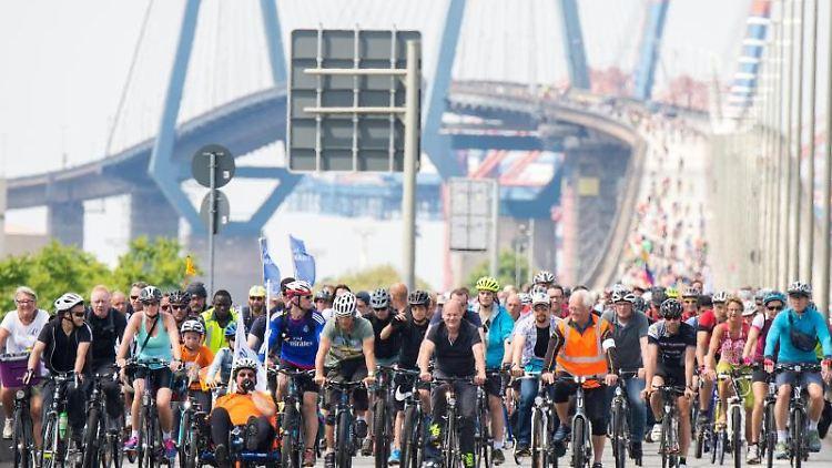 Teilnehmer einer Fahrradsternfahrt fahren mit ihren Fahrrädern über die Köhlbrandbrücke. Foto: Daniel Bockwoldt/Archivbild