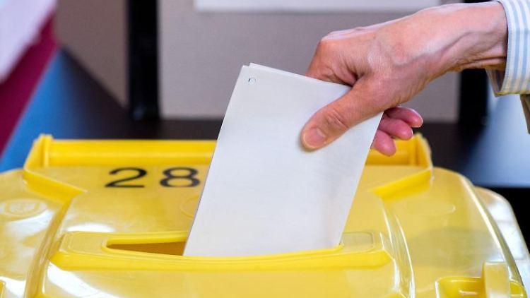 Ein Mann gibt einen Stimmzettel in Niedersachsen ab. Foto: Hauke-Christian Dittrich/Archivbild