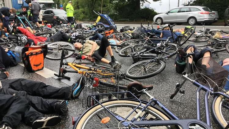 Mehrere Dutzende Menschen liegen mit ihren Fahrrädern auf der Straße. Foto: Thomas Müller