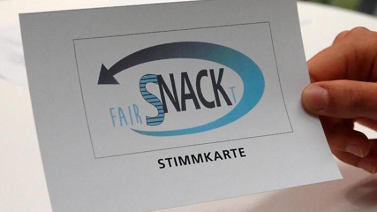 Ein Schüler des Gymnasiums Nackenheim zeigt eine Stimmkarte der Schülergenossenschaft