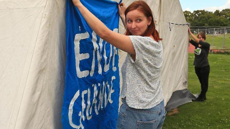 Kathrin Henneberger, Pressesprecherin von Ende Gelände, befestigt an einem Zelt ein Banner