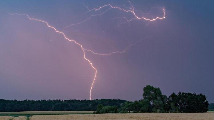 Blitze eines Gewitters erhellen den Abendhimmel. Foto: Patrick Pleul/Archivbild