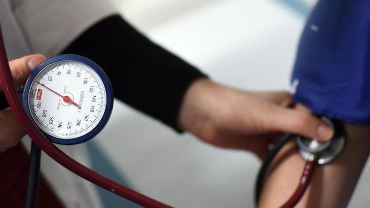 Ein Medizinstudent misst während einer Übung an einem Simulationspatienten den Blutdruck. Foto: Britta Pedersen/Archiv