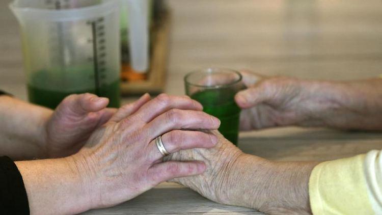 Eine Betreuerin fasst die Hände einer demenzkranken Frau. Foto: Ina Fassbender/Archivbild