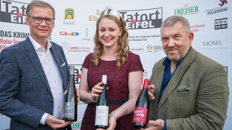 Günther Jauch (l.-r.), Mosel-Weinkönigin Laura Gerhardt und Dietmar Bär präsentieren die drei Festivalweine. Foto: Oliver Dietze