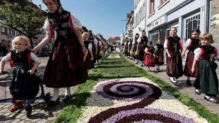 Trachtenträgerinnen in Hüfingen neben einem traditionellen Blumenteppich. Foto: Patrick Seeger/Archivbild