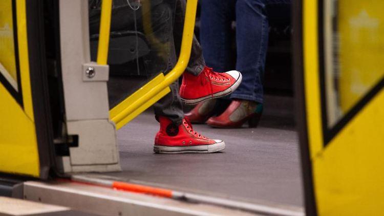 Eine Frau mit roten Schuhen sitzt in einer U-Bahn. Foto: Arne Immanuel Bänsch/Archivbild