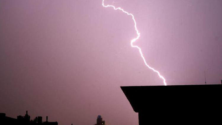 Blitze leuchten während eines Gewitters am Himmel. Foto: Julian Stratenschulte/Archivbild
