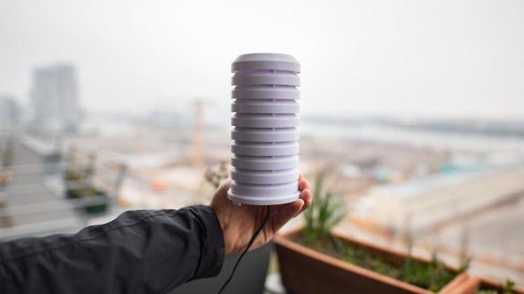 Ein Mann hält bei einem Pressetermin auf einem Balkon in der Hafencity ein Messgerät, das Daten zur Luftqualität sammelt. Foto: Daniel Reinhardt/Archiv