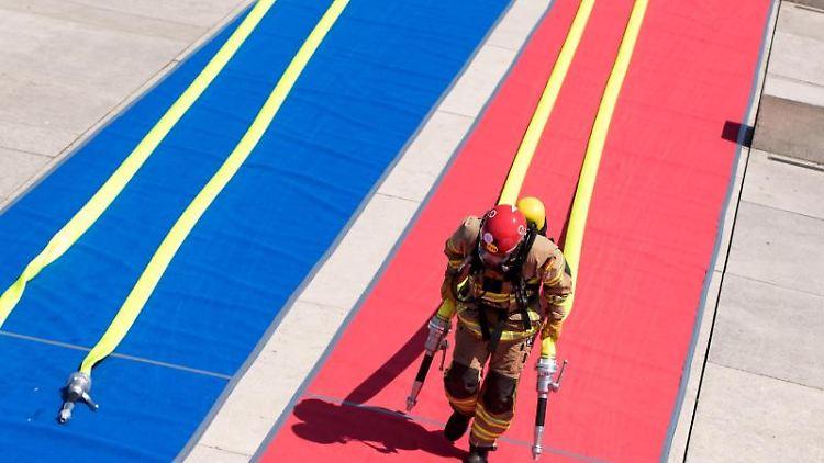 Ein Teilnehmer oder eine Teilnehmerin der Hamburger Firefighter Games zieht in voller Uniform Schläuche. Foto: Daniel Bockwoldt