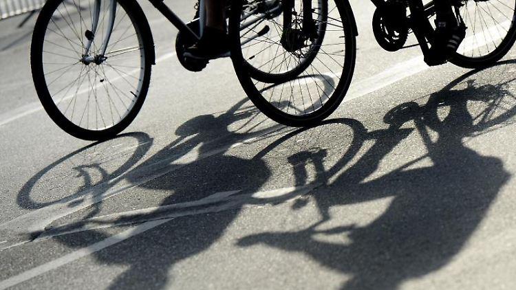 Die Schatten von zwei Radfahrern fallen auf eine Straße. Foto: Maurizio Gambarini/Archivbild