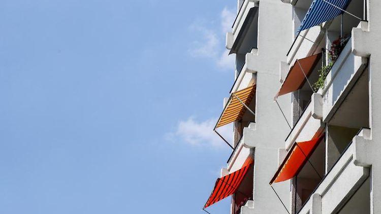 Die Sonne scheint auf mehrere Markisen an Balkonen eines Wohnhauses. Foto: Jan Woitas/Archivbild