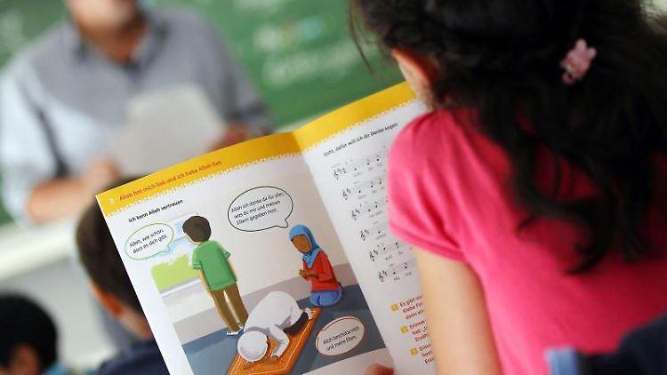 Ein Mädchen liest in einer Schule während des islamischen Religionsunterrichts in einem Schulbuch. Foto: Oliver Berg/Archivbild