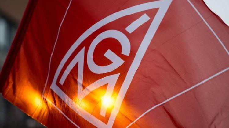 Eine Fahne mit dem Logo der IG-Metall wird geschwenkt. Foto: Lino Mirgeler/Archiv