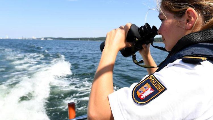 Cerina, Oberkommissarin der Wasserschutzpolizei, steht mit einem Fernglas am Heck des Polizeibootes. Foto:Carsten Rehder