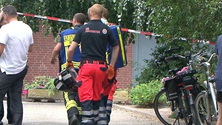 Rettungskräfte betreten ein Grundstück in Neuenkirchen. Foto: Nord-West-Media TV/dpa