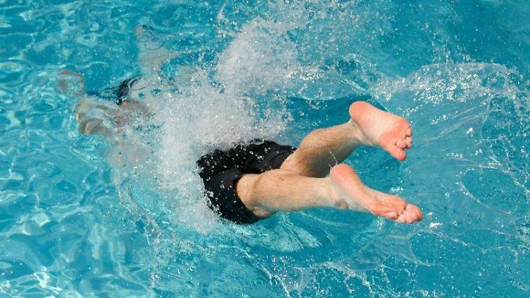 Ein Badegast springt ins Wasser. Foto: Sebastian Kahnert/Archivbild