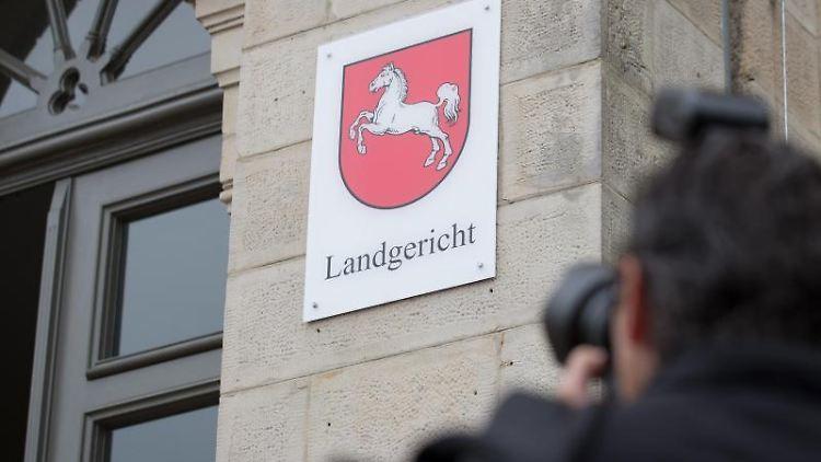 Ein Mann fotografiert den Eingang zum Landgericht. Foto: Friso Gentsch/Archiv