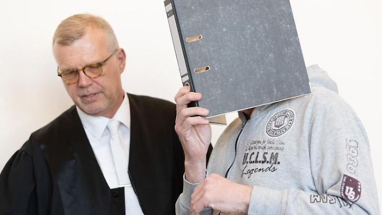 Einer der Angeklagten kommt mit einem Aktenordner vor dem Gesicht in einen Saal des Landgerichtes. Foto:Friso Gentsch