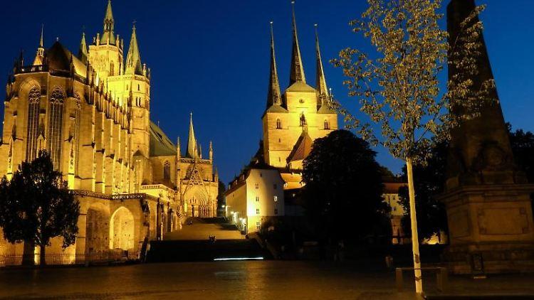 Der Erfurter Dom (l) und die St. Severikirche sind am Abend in der Dämmerung beleuchtet. Foto: Jens Kalaene/Archivbild
