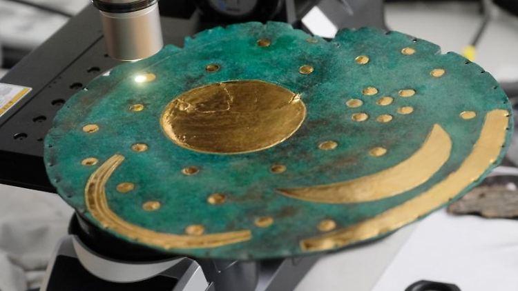 Eine Nachbildung der Himmelsscheibe unter einem Mikroskop. Foto: Sebastian Willnow/Archivbild