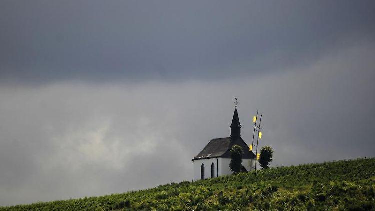 Dunkle Wolken hinter einer Kapelle in Schmallenberg. Foto: Marius Becker/Archivbild