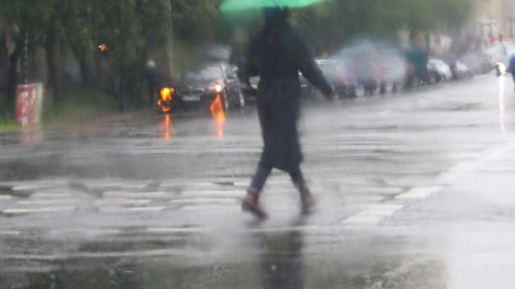 Eine Frau mit Regenschirm geht über eine Straße in Berlin. Foto: Wolfgang Kumm/Archivbild