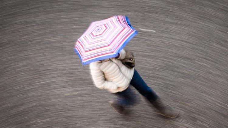 Eine Frau geht bei regnerischem Wetter durch Frankfurt. Foto: Frank Rumpenhorst/Archivbild