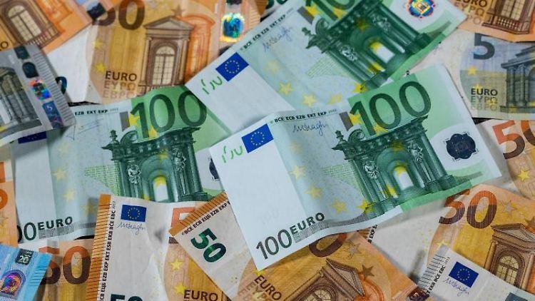 Euro-Geldscheine liegen auf einem Tisch. Foto: Jens Büttner/Archivbild