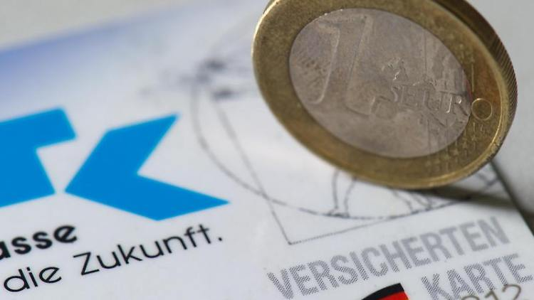 Eine Euromünze steht auf einer Versichertenkarte. Foto: Arno Burgi/Archivbild