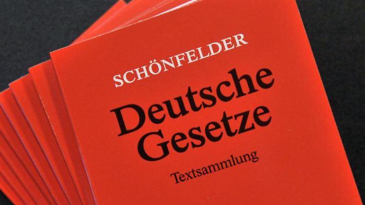 Gesetzestexte liegen auf einem Tisch. Foto: Martin Schutt/Archiv