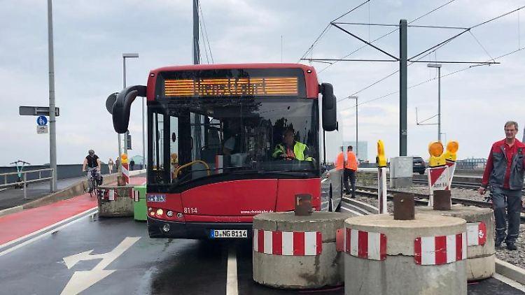 Ein Bus der Rheinbahn führt sich zwischen Betonpollern auf der Oberkasseler Brücke fest. Foto: Christine Wolff-Auster