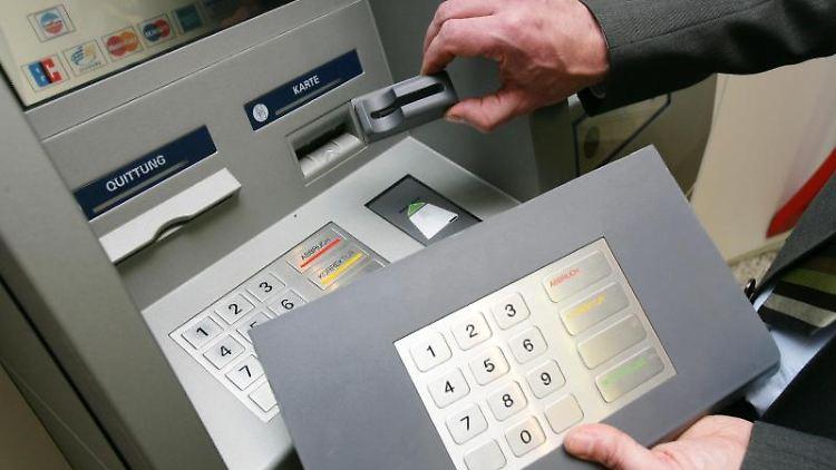Ein Mitarbeiter der Sparkasse demonstriert an einem Geldautomaten die