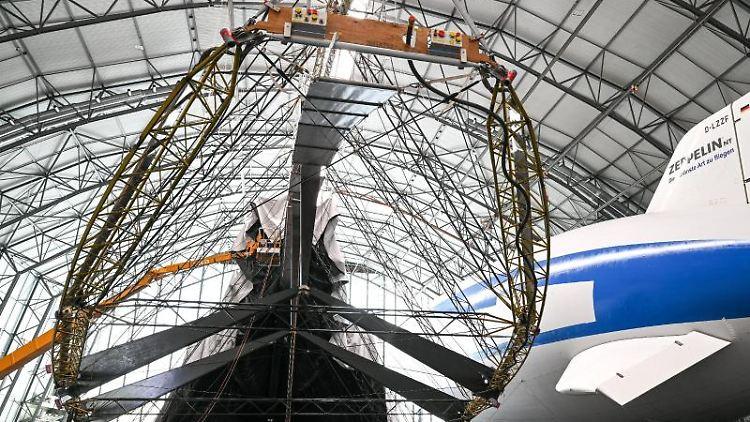 Besucher schauen sich den im Wiederaufbau befindlichen Zeppelin NT an, über den derzeit die Hülle gestülpt wird. Foto: Felix Kästle