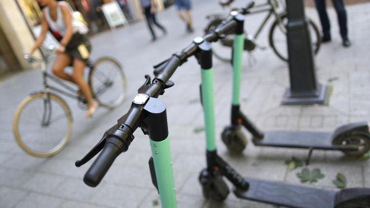E-Scooter stehen auf einer Einkaufsstraße. Foto: Martin Gerten/Archivbild