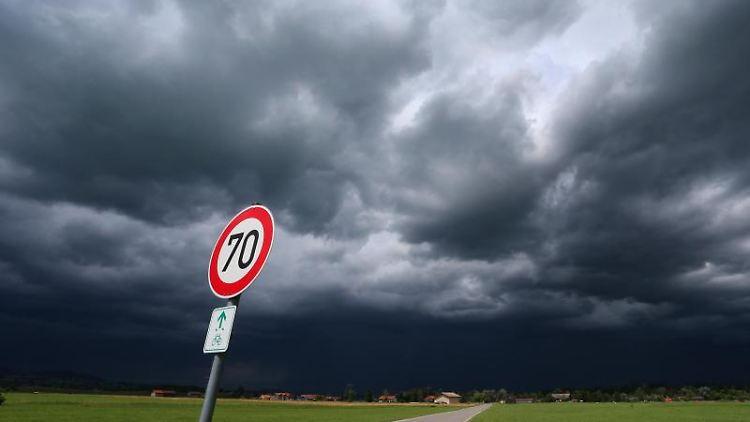 Eine dunkle Wolkenfront zieht hinter einem noch in der Sonne liegenden Feldweg auf. Foto: Karl-Josef Hildenbrand/Archiv