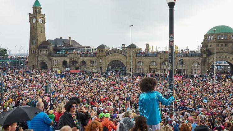 Zahlreiche Besucher des Schlagermoves stehen an den Landungsbrücken und feiern zur Musik. Foto:Georg Wendt