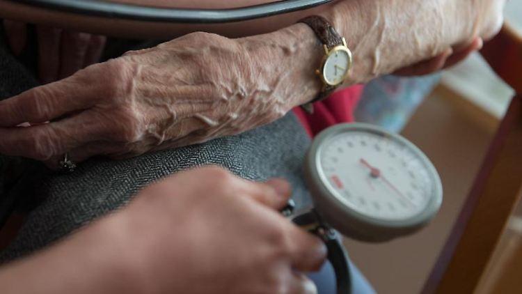 Eine Bewohnerin einer Seniorenwohnanlage bekommt den Blutdruck gemessen. Foto: Marijan Murat/Archivbild