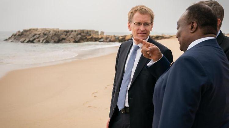 Daniel Günther (l., CDU) spricht am Strand mit Parlamentspräsident Fernando de Piedale Dias dos Santos (vorne). Foto: Patrick Kraft/Staatskanzlei Kiel