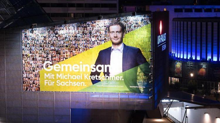 Ein Wahlplakat mit einem Foto von Ministerpräsident Kretschmer hängt an der Fassade des Kinos Ufa-Kristallpalast. Foto: Sebastian Kahnert
